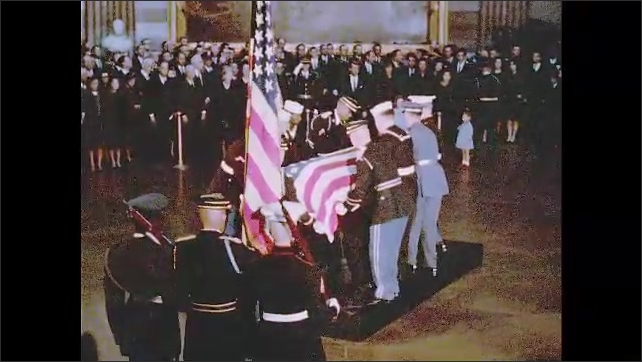 1960s: Men in uniform place casket on pedestal. Jackie Kennedy and children stand behind rope with Robert Kennedy.