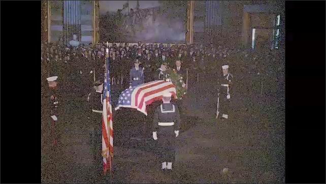1960s: Men in uniform surround casket. Men in uniform place wreath in front of casket. Jackie Kennedy kneels in front of casket.