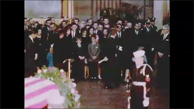 1960s: Casket lays on pedestal in capitol rotunda. Jackie Kennedy and Caroline Kennedy walk behind velvet rope. Men in uniform lead Jackie and Caroline Kennedy out of rotunda, other people follow.