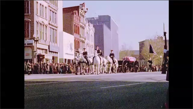 1960s: Street level footage of six white horses pulling the flag draped casket of Kennedy. A single soldier follows carrying a flag.