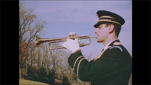 1960s: US Army Band trumpeter in dress uniform salutes. US Army Band trumpeter in dress uniform plays trumpet. US Army Band trumpeter in dress uniform lowers trumpet from mouth.