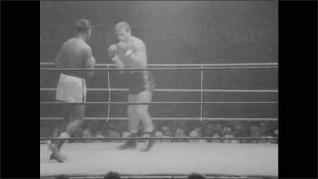 """1960s: Scoreboard at football game.  Caption reads """"Belgica.  SUGAR RAY ROBINSON, DERROTA A EMILE SARANS.""""  Boxing match.  Crowd watches."""