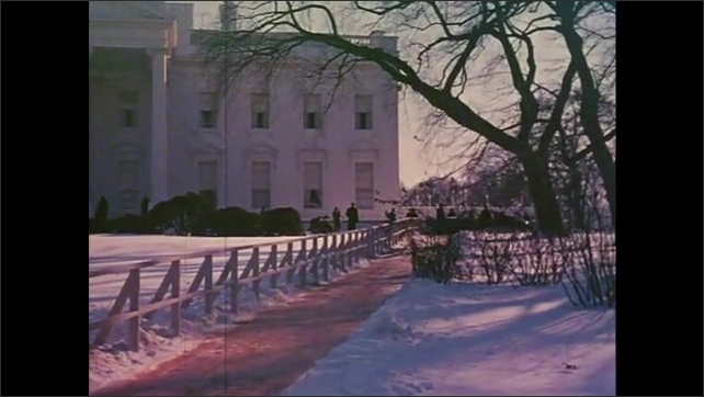 1960s: barren trees and snow-covered ground as cars drive along road, JFK and Jackie Kennedy walking in snow in front of White House