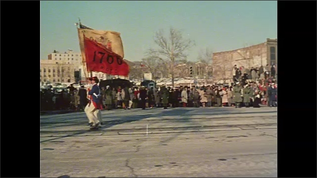 1960s: Pretty girl cheers on the side of the road for Inauguration Parade. Soldiers carrying 1776 flag march down street. Icy street with U.S. Capitol building in distance. Marching band.