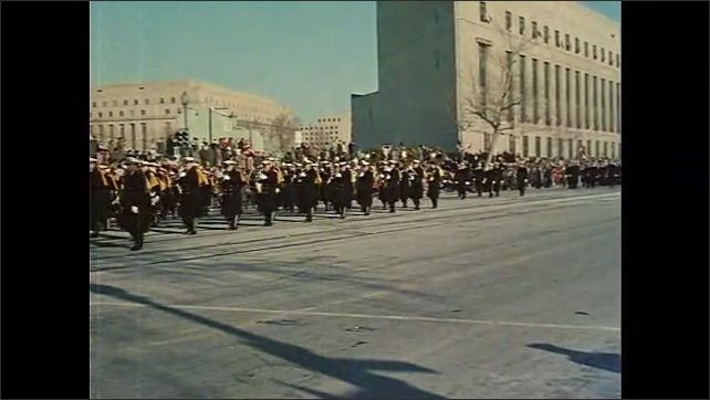 1960s: Soldiers in grey long coats carrying rifles march in Inauguration Parade. Military in navy blues march in parade.