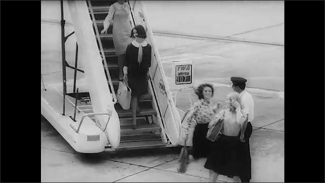 1960s: Title card. Passengers depart from plane down boarding stairs. Women stand on sidewalk and speak.