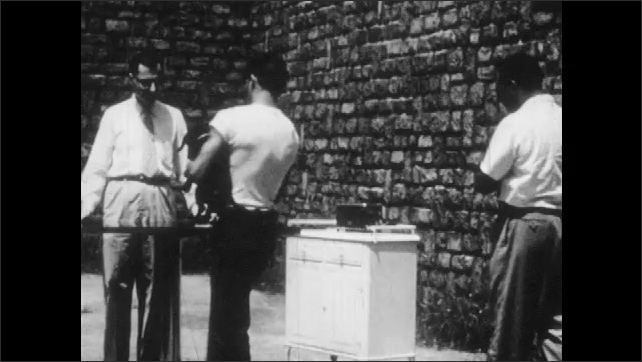 1950s: Police office takes note on pad of paper. Face of police officer. Men in courtyard, one man holding dog, other man places a dog on table, third man is veterinarian. Vet prepares syringe.
