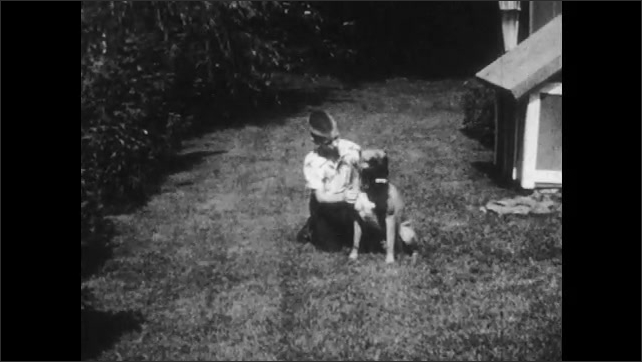 1950s: Man carrying dog takes paper from other man. Paper, certificate of canine rabies vaccination. Boy sits in yard petting dog. Boy jumps fence, dog watches from other side. Boy takes dog on walk.