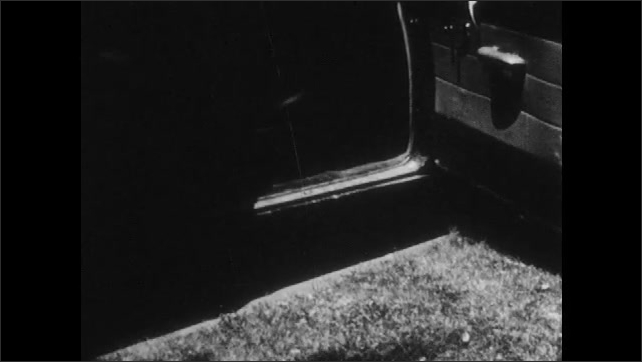 1950s: Man opens cage in back of pickup truck, retrieve dog from cage. Man walks dog to open car dog, dog jumps into car, man closes door. Man exits car with dog on leash.