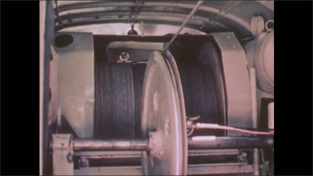 1950s: Man assemble a tool used to collect data from within an oil well. Cable unspools from a large wheel.