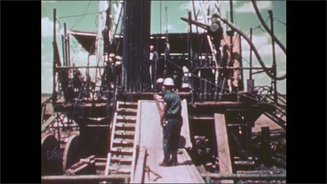 1950s: Two men in coveralls and hard hats maneuver a large instrument up a ramp and toward an oil well.