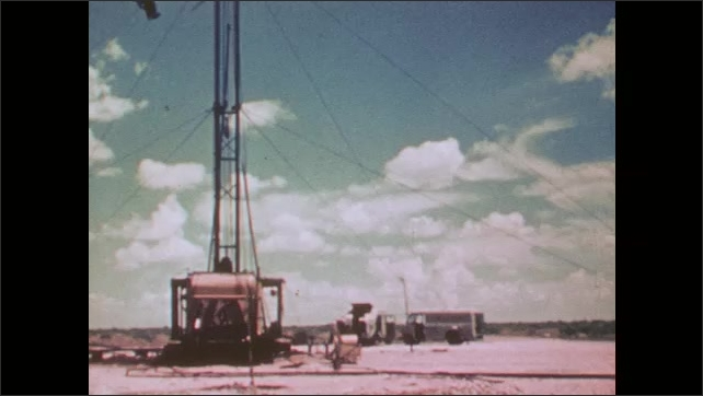 1950s: An oil well drill. An oil well in the sunset. A well in the daylight. A corrugated steel shed.