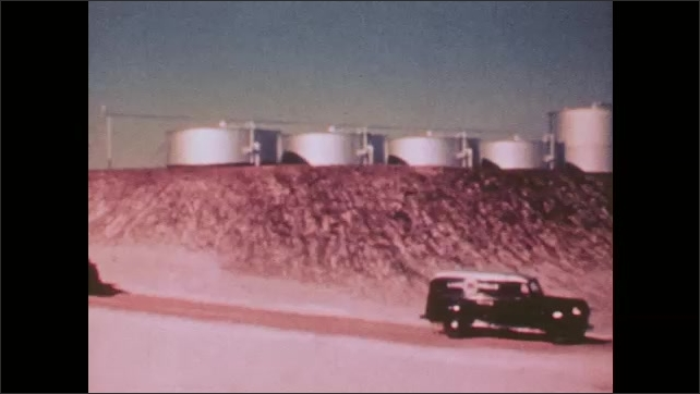 1950s: Two men use scientific equipment and record their findings. Two trucks drive through an oil field.