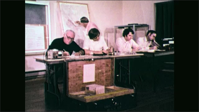 1970s: Men at table, man on phone. Hand writing by equipment. People working at table. Man talks into camera.