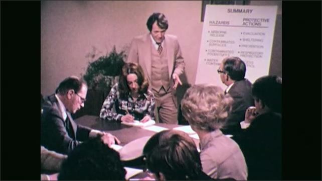 1970s: Man talking to people at table. Close up of man talking.