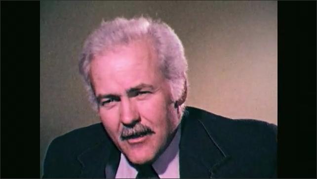 1970s: Close up of man talking. Man talking. Man talks, stands. Man stands, talks.