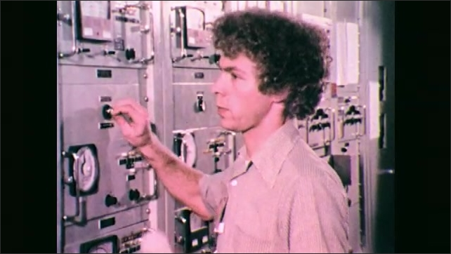 1970s: Man at electronic controls. Hand turns knob. Man at control panel, talks into phone. Close up of man, zoom out to men lying on ground.