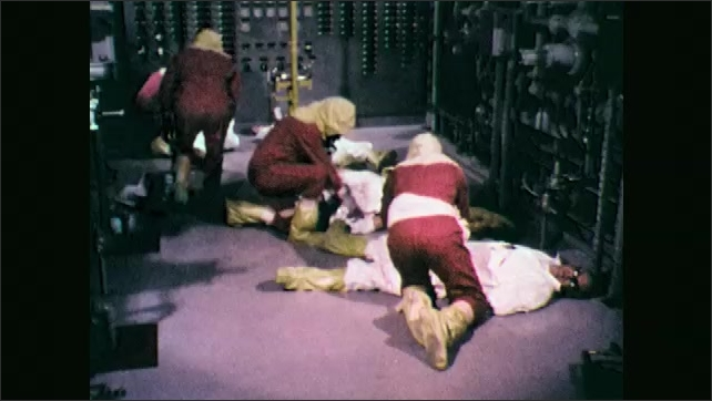 1970s: Men in hazmat suits enter room, inspect men on floor. Man at control panel. Hand pushes button. People climb into ambulance.