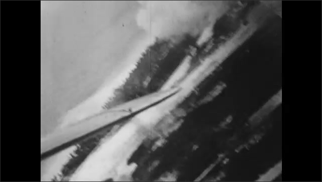 1940s: UNITED STATES: smoke from explosions on island. Overhead view of island from plane.