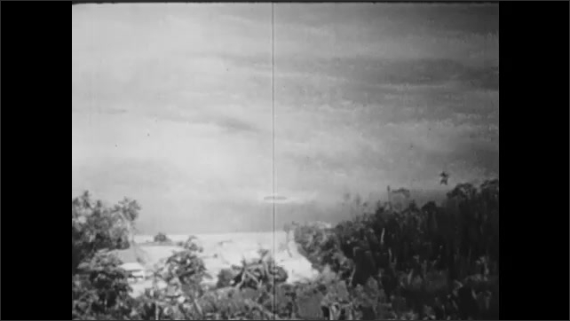 1940s: UNITED STATES: soldiers fire rockets. View across atoll from plane. Strike in trees.