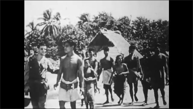 1940s: UNITED STATES: soldiers march from beach landing towards jungle. Soldiers round up villagers and prisoners of war. Children on island.