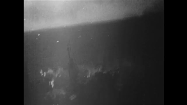 1940s: UNITED STATES: view of ships under attack from window of plane. Gun fire during raid.