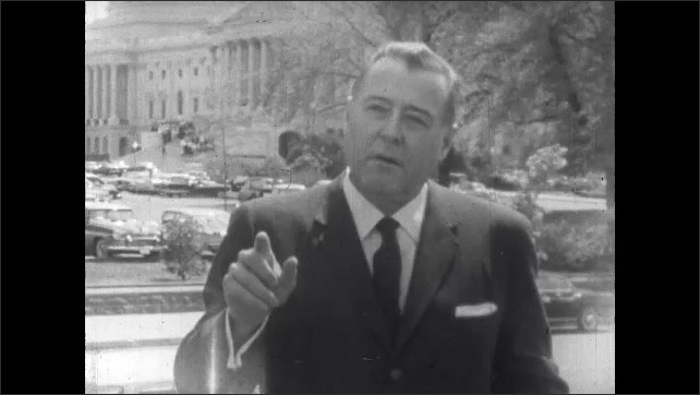 1960s: Man stands outside by capitol building, talks. Cars drive past on street.
