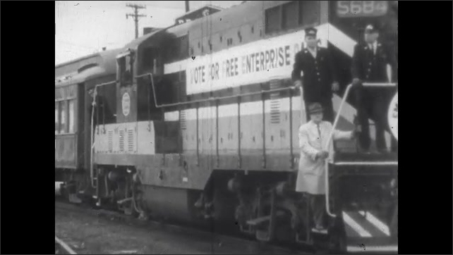 1960s: Men ride on the front of railroad engine. Men stand outside by railroad tracks.