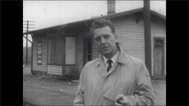 1960s: Man stands next to railroad tracks. Man takes pipe out of mouth, talks.