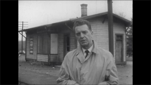 1960s: Man stands outside building, talks.