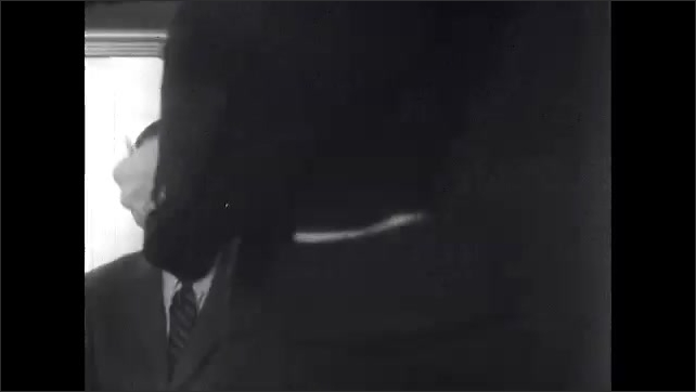 1960s: Men sit on train, talk. Man walks by, punches tickets.