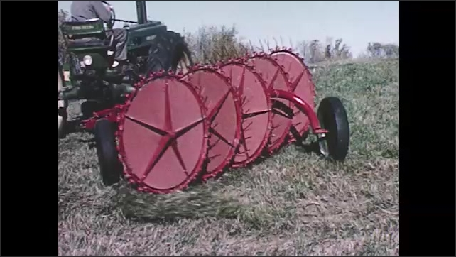 1960s: Man on tractor pulls agricultural wheel rake over hill of cut hay grass. Rake wheels spin to pile cut hay grass.
