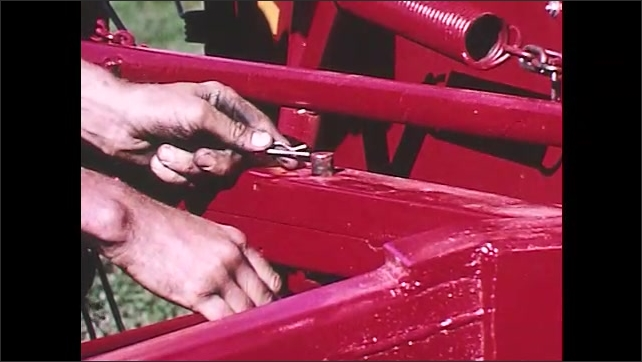 1960s: Hands pull linchpin from trailer hitch. Man adjusts wheel rake angle. Man re-hitches trailer and inserts linchpin. Man points to holes on adjustment bar.