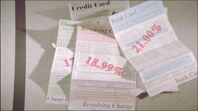 1990s: UNITED STATES: Revolving charge papers land on table. Summary of charges. Interest amounts