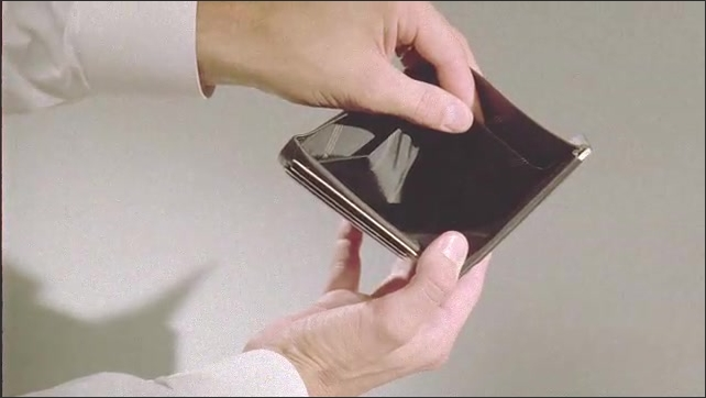 1990s: UNITED STATES: hands hold empty wallet to camera. Empty pockets inside wallet. Bank and store cards inside wallet