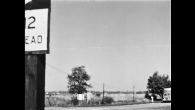 1950s: Road signs. Cars drive down road. Directional signage. Truck and car stop at intersection.