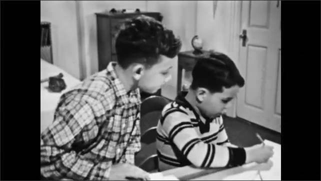 1950s: Two boys sit at desk, look at book, draw on paper. Boys measure space between playground equipment.