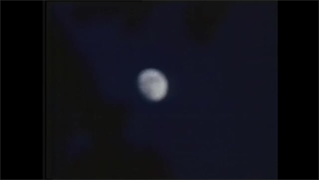 1970s: Side of spacecraft. Moon in night sky. Waves of water. Light shines at night. Moon in night sky. Person looks through telescope at moon.