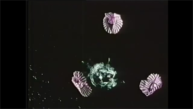 1970s: Spacecraft capsule parachutes into sea. Spacecraft floats on water with astronauts in boat next to it.
