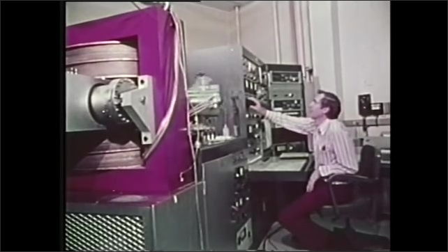 1970s: Scientists look through window of containment box at moon rock. Moon rock. Man operates science equipment. Image of moon rock.