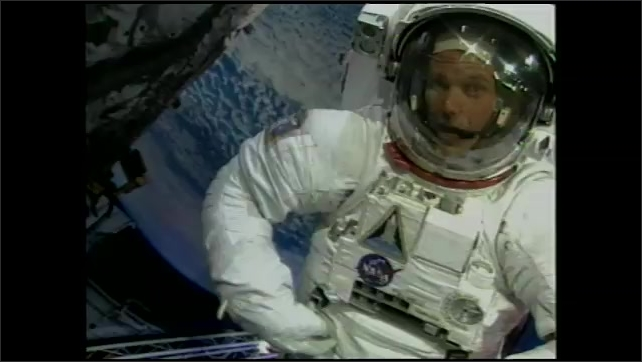 2000s: Man in space suit talks while demonstrating lack of mobility.