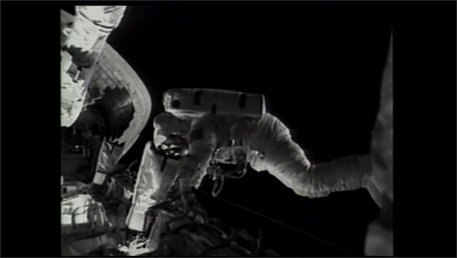 2000s: Astronaut on space walk inside open cargo bay of Space Shuttle. Man wearing headset inside airplane talks while holding up picture of astronaut on space walk. Astronaut in training.