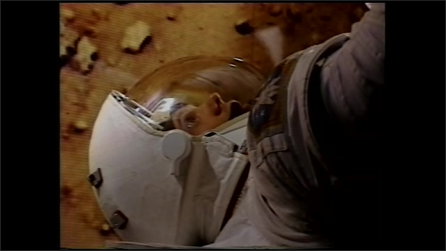 2000s: Astronaut in space suit trains in airplane in zero gravity. Man in space suit talks with image of Mars behind him. Man trains in airplane. Man talks with image of Mars behind him.