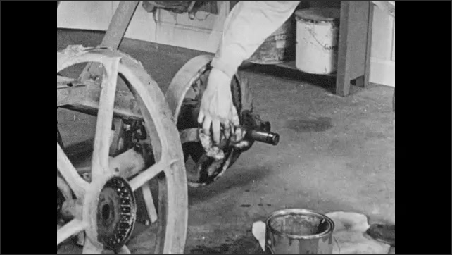 1950s: Dissolve, man rubs wheel ratchets with cloth, cleans axle, rubs oil on part of wheel joint.