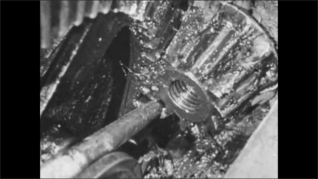 1950s: Hands turn gear on mower. Close up of screw turning. Machine part loosening. Man removes part from mower.