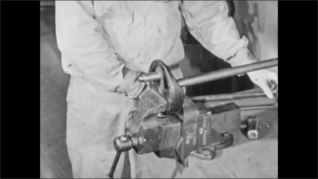 1950s: Close up, saw cutting through metal bar. Hands saw through bar, hit bar with hammer. Hammer knocks bar from wheel.