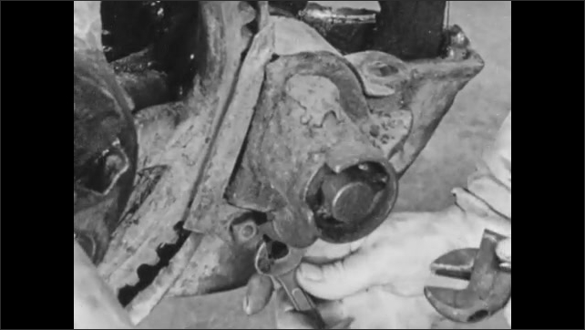 1950s: Close up, remove parts from mower axle. Hands unscrew bolt.
