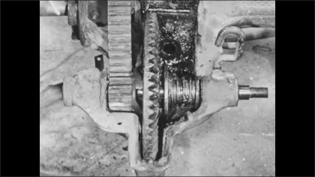 1950s: High angle view of mower axle, hands loosen parts with wrench.
