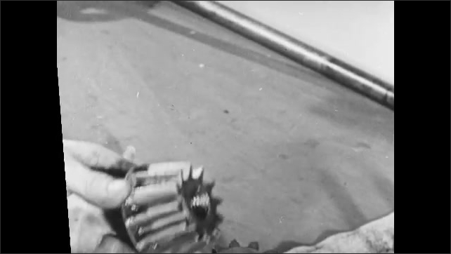 1950s: Close up, hand holds up metal machine parts. Hands insert rod into mower parts.