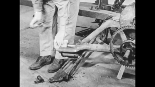 1950s: Man puts machine parts on ground. Close up, hands put part into mower. Man hammers part. Close up of hammer hitting part. Hammer hits block of wood on mower.